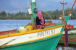 Cham woman wearing traditional krama head scarf sitting in prow of colourful fishing boat, dawn on the Sanke river, Kampot, Cambodia.