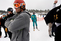 Competitors' watch a race at the Whitefish Skijoring World Championship event in Whitefish, Montana, USA.  Skijoring is a competitive sport in which a person on skis navigates an obstacle course while being pulled behind a galloping horse.