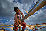 Fabian Cantillo works on a rafter of his family's new house at Tarau-Paru, a Pemon indigenous village just inside Brazil. Cantillo and his family are refugees, having fled from Venezuela early in 2019 after new outbreaks of violence between the Venezuelan military and Pemon villagers.