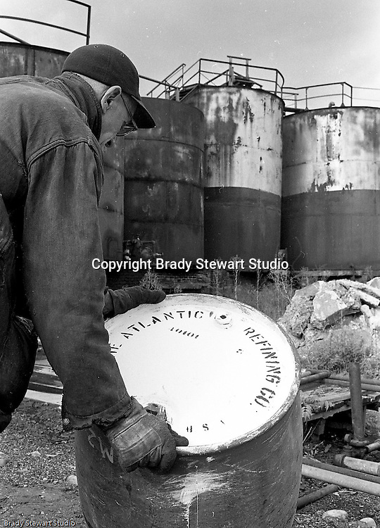 Lawrenceville PA: Location photography at the Atlantic Refining site at 5733 Butler Street. View of a workman moving a barrel full of oil.<br />