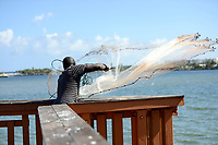 Net fisherman tossing his net into the intracoastal  waterway near Boynton Beach, Florida. He was actually catching more fish than many nearby anglers with their fancy fishing rods and bait, and was fishing to feed his family.