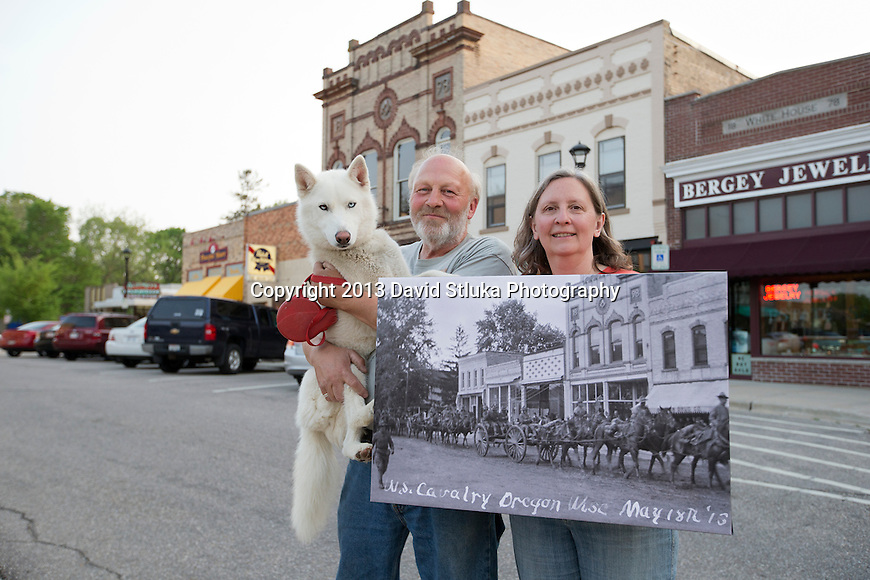 Mason's On Main owners Jerry and Bonnie Thiel pose with a historic photo from May 18th, 1915, the 98th anniversary of the U.S. Calvary marching through downtown Oregon, May 18th, 2013, in Oregon, Wisconsin. (Photo by David Stluka)