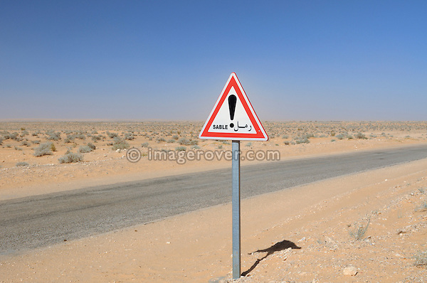 Africa, Tunisia, between Ksar Rhilane and Douz. Road sign warning of sand drifts.