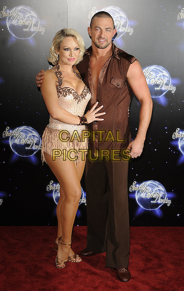 KRISTINA RIHANOFF & ROBIN WINDSOR .At the Strictly Come Dancing Launch Show TV recording, London, England, UK, September 8th 2010..full length  halterneck top costume dress  beige sparkly strappy gold sandals brown sleeveless shirt tassels .CAP/CAN.©Can Nguyen/Capital Pictures.
