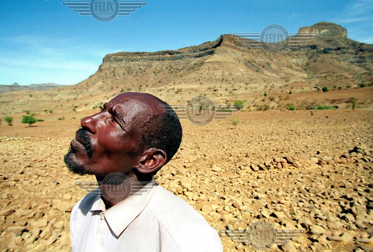 © Sven Torfinn / Panos Pictures..Ethiopia, Wag Hamra, Bilak village, December 2002. Drought...Teshoma Abera standing in his barren, stony and infertile field. Looking up at the sky, he explains there have been just two days of rain all year. His crops failed dramatically, leaving his family with just one month's supply of food, after which they will be dependent on food aid.