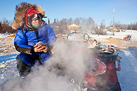 Gerald Sousa eats a meal out of a seal-a-meal bag as he waits for his dog water to get hot at the Kaltag checkpoint during the 2010 Iditarod