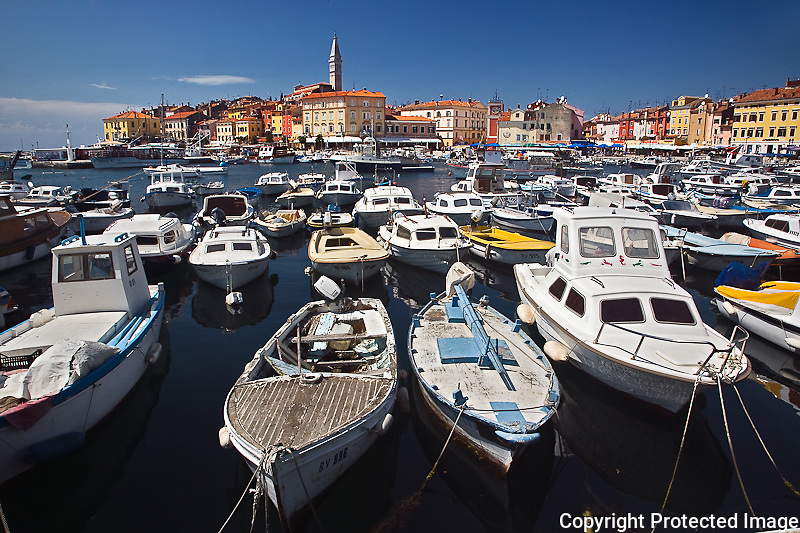 Boats docked in harbor in front of distant Cathedral of St. Euphemia, Rovigno, Croatia
