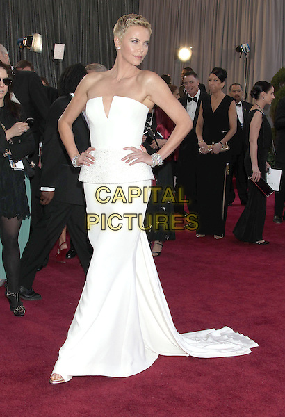 Charlize Theron (wearing Dior Couture).85th Annual Academy Awards held at the Dolby Theatre at Hollywood & Highland Center, Hollywood, California, USA..February 24th, 2013.oscars full length dress white strapless peplum short cropped hair pixie cut hands on hips train .CAP/ADM/RE.©Russ Elliot/AdMedia/Capital Pictures. Oscars