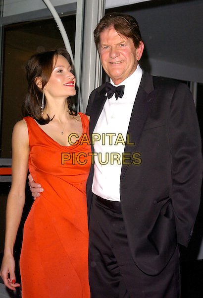 JOHN MADJESKY & GUEST.The Red Cross London Ball, The Room By The River, London, England..November 21st, 2007.half length red dress black tuxedo hand in pocket .CAP/CAN.©Can Nguyen/Capital Pictures