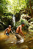 BELIZE, Hopkins, kids swim near a waterfall at the end of the Ben's Bluff Trail, Cockscomb Basin Wildlife Sanctuary
