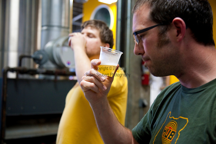 Hopworks Urban Brewery located in Southeast Portland is Portland's first Eco-Brewpub and offers all organic handcrafted beers, fresh local ingredients used for its menu items and located in a refurbished, sustainable building.  Pictured is owner/brewmaster Christian Ettinger and assistant Brewmaster Ben Love tasting quality control off the filter Organic Hub Lager, a Chech StylePilsner,  in the brewery which is located downstairs from the restaurant.