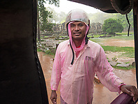 A Tuk Tuk driver at the Bayon Temple during a heavy rain storm, Cambodia