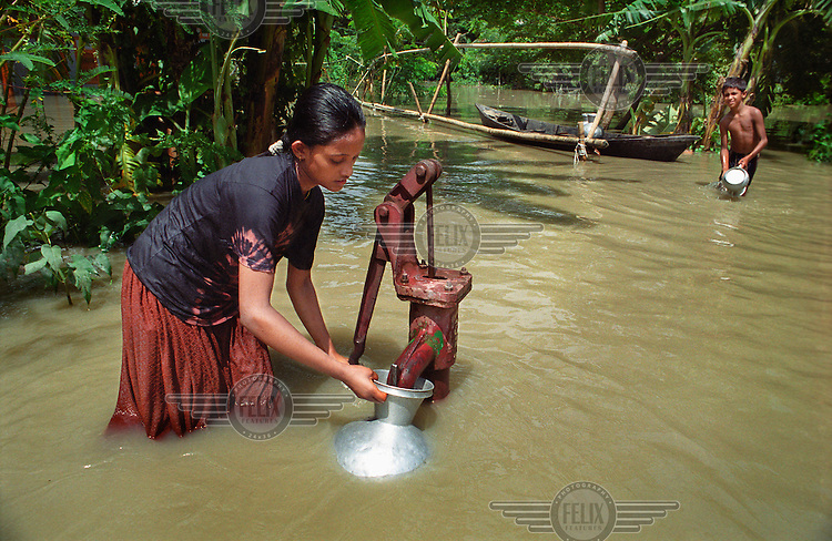 Girl collecting clean water from a pump in her flooded village. Monsoon rains caused flooding in 40 of Bangladesh's 64 districts, displacing up to 30 million people and killing several hundred.