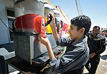 "A boy sells an iced drink on the ""Avenue des Champs-Élysées""--the main commercial street in the Zaatari refugee camp near Mafraq, Jordan. Established in 2012 as Syrian refugees poured across the border, the camp held more than 80,000 refugees by 2015, and was rapidly evolving into a permanent settlement, with shops along this street selling everything the refugees could want. The ACT Alliance provides a variety of services to refugees living in the camp."