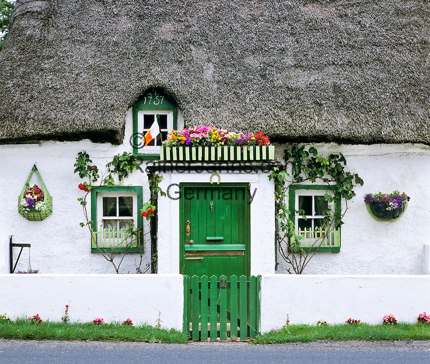 Ireland, County Kilkenny, Front of typical Irish cottage | Irland, County Kilkenny, Hausfront eines typisch irischen Cottages mit Reetdach
