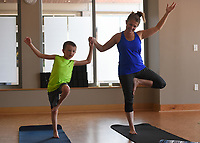 "NWA Democrat-Gazette/CHARLIE KAIJO Missy Wooldridge (right) and Blaine Wooldridge, 6, of Bella Vista perform a stretch during a kids yoga class, Monday, July 8, 2019 at Yoga Story in Bentonville. <br /> <br /> ""It helps them to learn to breath, pay attention to their bodies, work through emotions and sensations,"" said instructor Kari Pace describing the benefits of yoga for kids. ""I was a very anxious kid so it would have been nice to have a technique like this. It's fun to share it with my kids and other kids."""