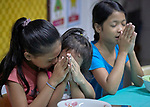Children pray before a meal in the United Methodist Church in the Parola neighborhood of Tondo, a poor section of Maniila, Philippines. Nursing students from the Mary Johnston College of Nursing regularly visit the neighborhood to do health education and monitor the health of residents, at the same time running  a feeding program for neighborhood children.<br /> <br /> The nursing school is supported by United Methodist Women.