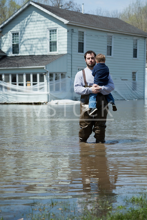 Man with son standing in front of house surrounded by floodwaters