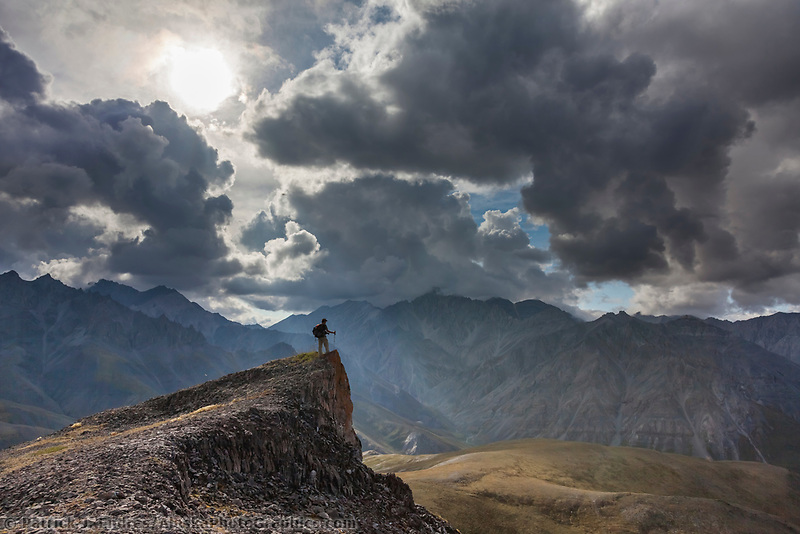 Hiker in the Brooks Range mountains bordering the west side of the Marsh Fork of the Canning River in the Arctic National Wildlife Refuge in the Brooks Range mountains, Alaska.