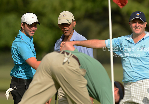 Prime Minister John Key of New Zealand, right, high fives his son, Max Key, left, as United States President Barack Obama, center, looks on at the 2nd green, Marine Corps Base Hawaii's Kaneohe Klipper Golf Course, Kaneohe, Hawaii, January 2, 2014.<br /> Credit: Cory Lum / Pool via CNP