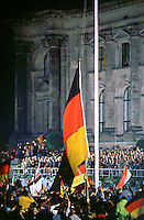 DEUTSCHLAND, 03.10.1990.Berlin - Mitte.Staatsakt und offizielle Feiern zur deutschen Wiedervereinigung: Hissen der riesigen deutschen Flagge am Reichstag. Daneben sind auch schon die Nazis mit der Reichskriegsflagge..State act and official celebration of German reunification: Raising the giant German flag at the Reichstag. In the background the tribune with chancellor Helmut Kohl..© Martin Fejer/EST&OST