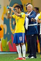 Neymar sprays water in his face as Brazil head coach Luiz Felipe Scolari shouts behind him