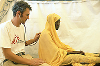 Sudan. West Darfur. Ryiadh. Ryiadh is located on the outskirts of the town of Al Geneina and is a camp for internally displaced people (IDP)) from the civil war. The german doctor Tibor Sasse from the non-governmental organization (ngo) Médecins sans Frontières (MSF) Switzerland checks during a medical visit the health of a  young woman whose head is covered with a yellow veil . © 2004 Didier Ruef