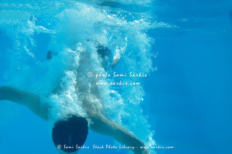 Teenage boy (17) taking the plunge in pool, underwater view