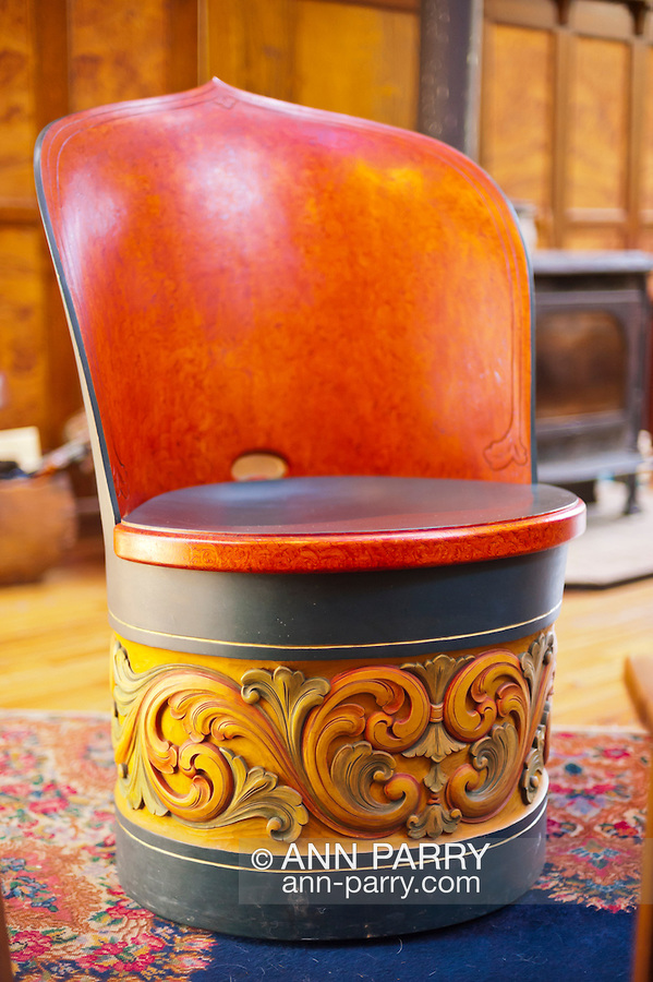 Hancarved wood chair, barrel shape with seat back, on living room rug, Auguust 2012