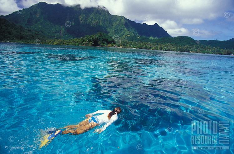 Woman snorkeling on reef in clear water in Raiatea, Tahiti, French Polynesia