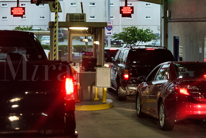 Cars wait to pay fee at a parking garage exit.