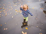 Toddler on wet fall afternoon in puddle on driveway covered with leaves.