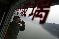 CHINA. Chongqing Province.  A passenger on a boat passing through the 3 Gorges. The flooding of the three Gorges, by damming the Yangtze near the town of YiChang, has remained a controversial subject due to the negative environmental consequences and the displacement of millions of people in the flood plain. The Yangtze River however is reported to be at its lowest level in 150 years as a result of a country-wide drought. It is China's longest river and the third longest in the world. Originating in Tibet, the river flows for 3,964 miles (6,380km) through central China into the East China Sea at Shanghai.  2008.