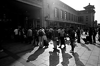 Daytime landscape view of people standing in line to enter the train station building at the B?ij?ng Zhàn in D?ngchéng Q? in Beijing.  © LAN