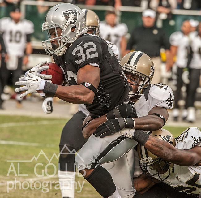 Oakland Raiders fullback Jeremy Stewart (32) tackled by Saints defense on Sunday at O.co Coliseum in Oakland, CA.  The Saints defeated the Raiders 38-17..