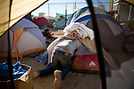 RENO, NV - OCTOBER 6:  A homeless man struggles to get out of his small tent in a tent city for the homeless in downtown Reno, Nevada October 6, 2008. The City of Reno set up the tent city when existing shelters became overcrowded as Nevada struggles with one of the highest unemployment rates in the country. (Photo by Max Whittaker/Getty Images)