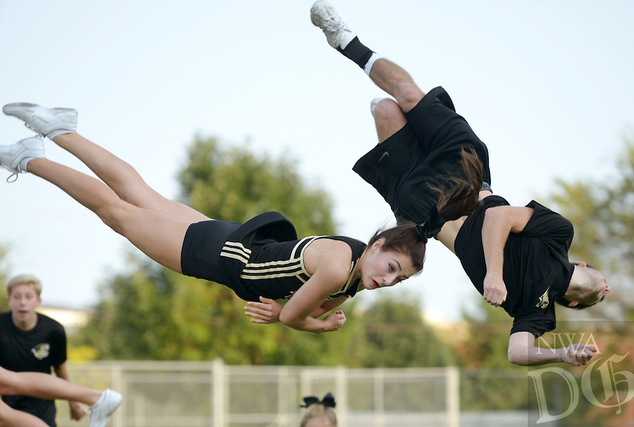 NWA Democrat-Gazette/BEN GOFF @NWABENGOFF<br /> Chloe Christian and Ben Malatesta flip throughout the air on Saturday Aug. 22, 2015 as the Bentonville varsity cheer squad performs during Tiger Pride night in Bentonville's Tiger Stadium.