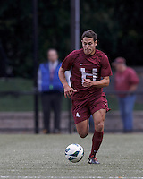 Harvard University defender Ross Friedman (4) brings the ball forward. Boston College (white) defeated Harvard University (crimson), 3-2, at Newton Campus Field, on October 22, 2013.