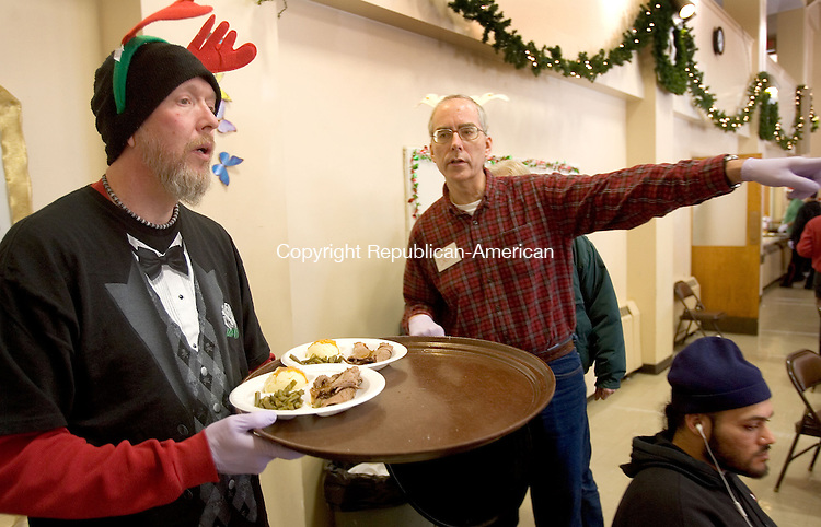 WATERBURY CT. 25 December 2013-122513SV07-From left, Ronald Balromitis and Dennis Guillaume both of Waterbury serve dinner during the annual Joy of Christmas Dinner event held at the First Congregational Church in Waterbury Wednesday. Members and friends of the First Congregational church prepared and shared a Christmas feast with those who have no place else to go or share the joys of the holiday. <br /> Steven Valenti Republican-American