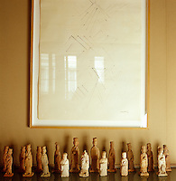 In the dining room an antique Chinese chess set is displayed beneath a framed contemporary monochrome print