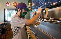Brantey Wright, 'Beertender', pours a NWA Pint Day Hazy Pale Ale Saturday, June 20, 2020, for a customer at Natural State Beer Company in Rogers. The Hazy Pale Ale was brewed by Fossil Cove Brewing Company in Fayetteville for the second annual NWA Pint Day Saturday. Many breweries in Northwest Arkansas took part in the event to celebrate local brewers and breweries. A portion of Pint Day sales will help members of the craft brewing community affected by covid-19. Go to nwaonline.com/200621Daily/ to see more photos.<br /> (NWA Democrat-Gazette/Ben Goff)