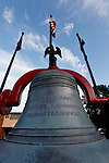 An eagle figure atop a bell with blue skies and flags in the background