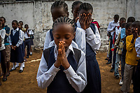 MONROVIA, LIBERIA - FEBRUARY 17: Students pray during devotion at school morning assembly, on the second day of classes, since schools closed 6 months ago, due to the Ebola outbreak, at the C.D.B. King Elementary School on February 17, 2015 in Monrovia, Liberia. Though Ebola cases have receded into the single digits in Liberia, lingering fear and a depressed economy have dampened the turnout at schools. Many have yet to reopen, having failed to meet the minimum requirements put in place to prevent the transmission of the virus. Many of those that have reopened – like C.D.B. King, which, though located in the center of the capital, lacks electricity and running water, and has only a few toilet stalls for a student population that numbered 1,000 before Ebola — are struggling.<br /> Daniel Berehulak for The New York Times
