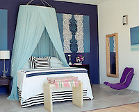 Navy blue and white stripes are contrasted with turquoise bed hangings in this cool and tranquil bedroom