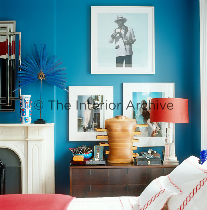 Three large chrome-framed prints are displayed against the deep turquoise walls of the master bedroom above a chest of drawers laden with interesting objets