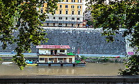 Fine Art Landscape Print Photograph. The foliage of the trees, and the textures of the walls helped to   frame this interesting scene of a houseboat that is on the Tiber river.<br /> The lone male occupant in the door frame of the houseboat makes the viewer take a closer look at the details of this image and his lifestyle.