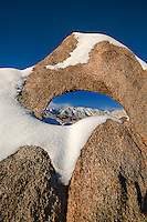 711700264 snow drapes over a wind erosion created granite arch that frames mount whitney and the eastern sierras in the alabama hills blm protected lands in central california