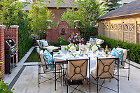 A table is laid for lunch and set on an outside terrace in a formally styled garden.
