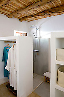 A partition separates bathroom and bedroom and also serves as a wardrobe
