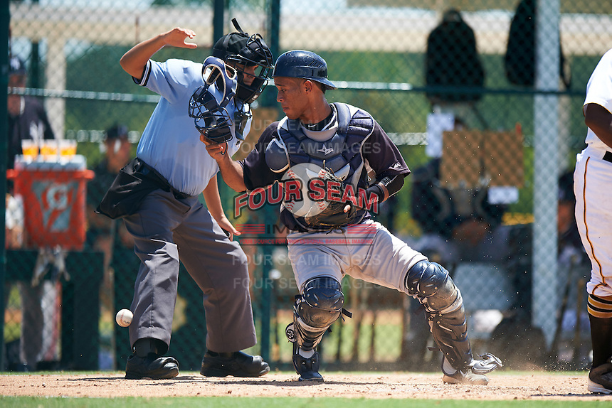 GCL Yankees East catcher Algeni Mateo (26) looks for a passed ball as umpire Josh Gilreath tries to move out of the way during a game against the GCL Pirates on August 15, 2016 at the Pirate City in Bradenton, Florida.  GCL Pirates defeated GCL Yankees East 5-2.  (Mike Janes/Four Seam Images)